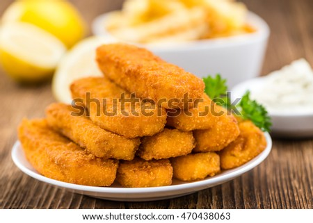 Some fried Fish Sticks (selective focus) on an old wooden table