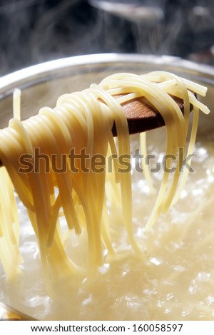 Some spaghetti are cooking in hot water