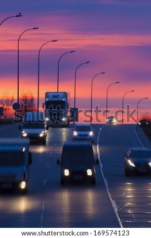 Some vehicles in motion in an spanish road. Night traffic. Night transport