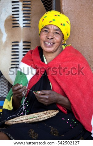 South Africa, Gauteng, Lesedi Cultural Village  - 04 July, 2015. Beautiful African Zulu woman Bantu nation is weaving a bead jewelry. Traditional handmade costume, headdress and blanket.