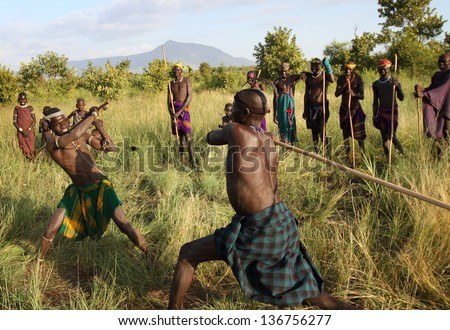 SOUTH OMO - ETHIOPIA - DECEMBER 21, 2011: Unidentified Mursi Donga warriors on December 21, 2011 in South Omo, Ethiopia. A 5-year resettlement program started 2011 threatens the tribes in Ethiopia.