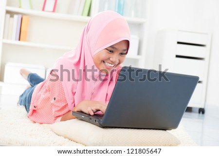 Southeast Asian teenager surfing internet. Muslim teen using notebook at home