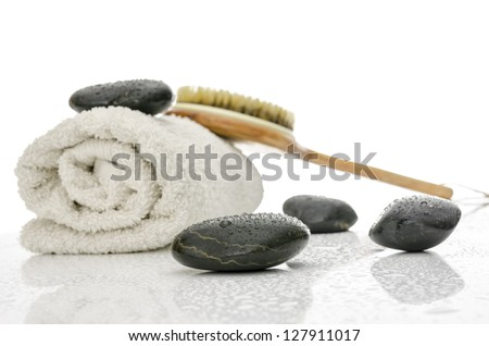 Spa and wellness setting with massage stones, brush and a towel. On a white table with water drops.