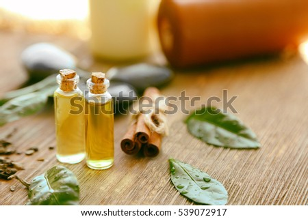 Spa composition with tea oil in small glass bottles and fresh leaves