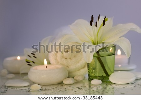 Spa concept (flowers, towel, candle and pebbles). Purple background