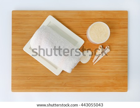 Spa herbal compressing ball with towels and Salt Scrub, Spa concept on bamboo board against white background, Top view