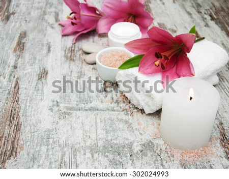 Spa products with pink lily on a old wooden background
