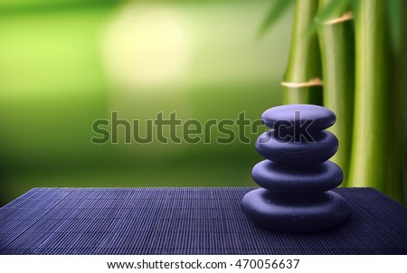 Spa setting of blue stones with green bamboo background