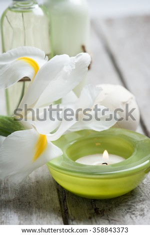 SPA still life, green lit candle, bath products, wooden background