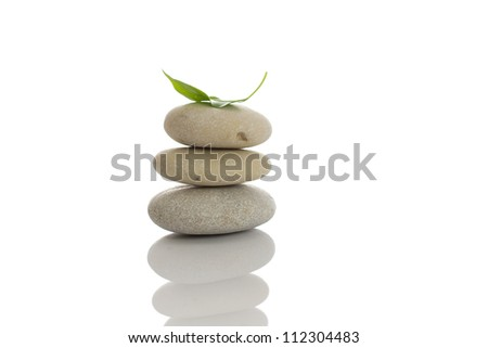 Spa stones and green leaf, isolated on white background.