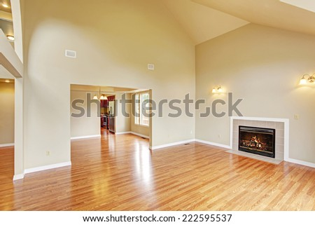 Spacious living room with high vaulted ceiling,  fireplace and new hardwood floor in empty new house