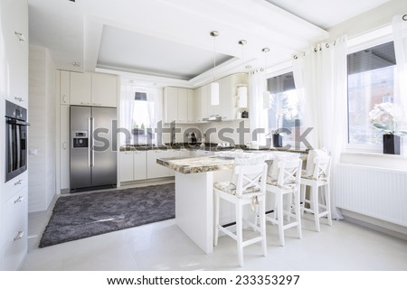 Spacious,white kitchen with counter-top dining place
