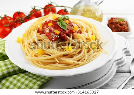 Spaghetti with tomato sauce and cheese on white plate, on color wooden background