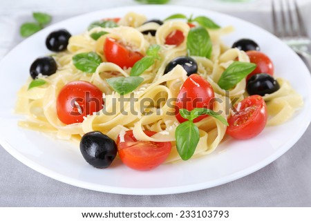 Spaghetti with tomatoes, olives and basil leaves on plate closeup