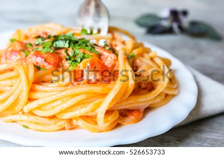 Spaghetti with vodka sauce topped with parmesan cheese and fresh parsley on a plate, selective focus