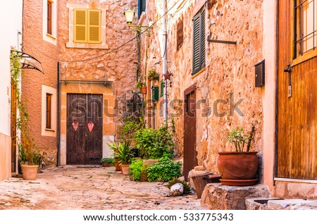 Spain Majorca typical old village with flower pots in mediterranean patio.