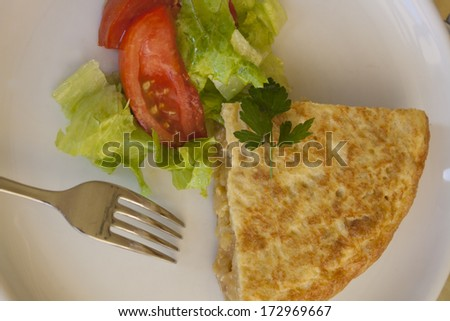 Spanish omelet on white plate with salad, cooked with potato, egg, olive oil and salt.