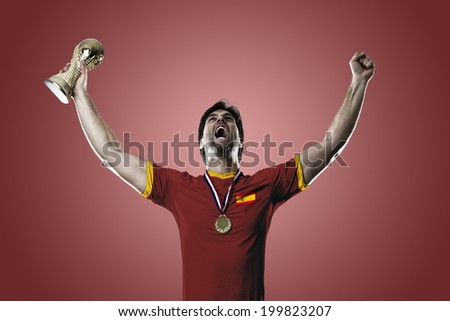 Spanish soccer player, celebrating the championship with a trophy in his hand. On a red background.