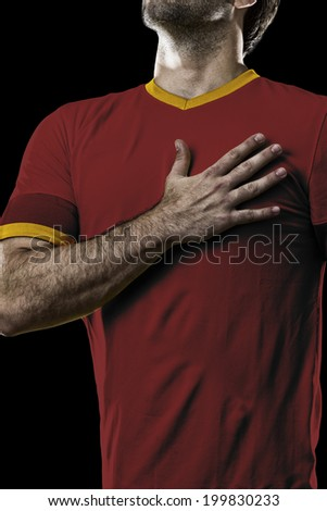 Spanish soccer player, listening to the national anthem with his hand on his chest. On a black background.