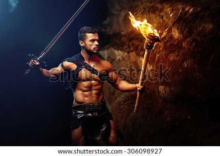 spartan on a dark background rocks, warrior, fighte holds a raised sword and burning torch, spartan looking ahead, black leather bandage on hips, athletic body.