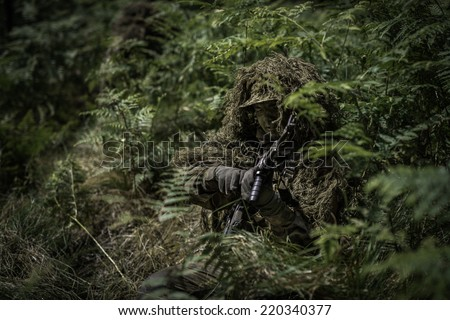 Special forces soldier during change of ammunition clip.