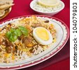 Special occasion Indian curry, lamb biryani with egg, coriander, and red, yellow and white rice. - stock photo