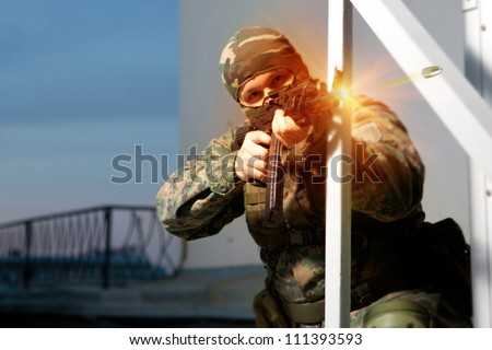 Special squad soldier is shooting from the Kalashnikov machine gun.
