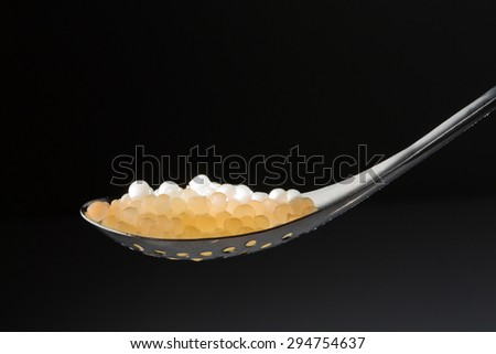 Spherification of melon juice served with a metal spoon