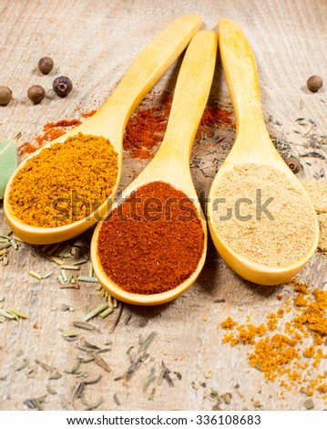 Spice powder on a wooden background. Paprika, curry and ginger on a wooden spoon.