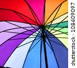 spokes and wires view of a rainbow and multicolour umbrella - stock photo