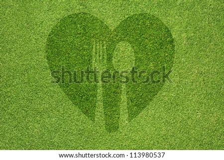 Spoon with heart icon on green grass texture and background