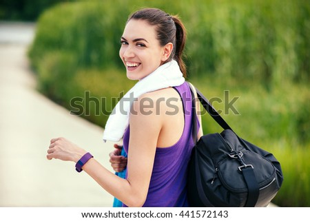 Sport. Beautiful smiling happy young woman before or after workout and running look from back on nature background.With purple t-shirt and white towel.