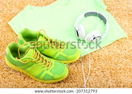 Sport clothes, shoes and headphones on color carpet background.