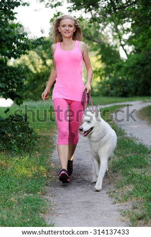 Sport girl with Huskies in a park