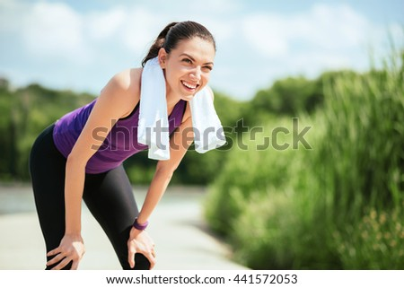 Sport. Happy smiling attractive woman making outdoor before or after workout and running in park. With purple t-shirt and white towel on nature background.