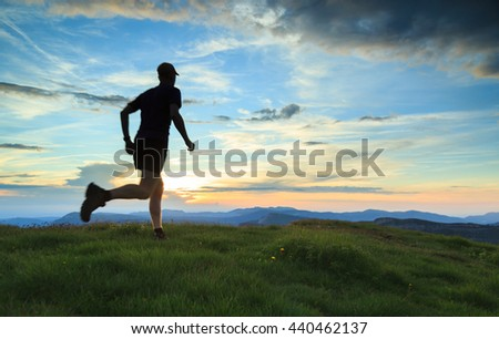 Sports concept with motion blur: Athlete trail running in the mountains during a nice sunset.