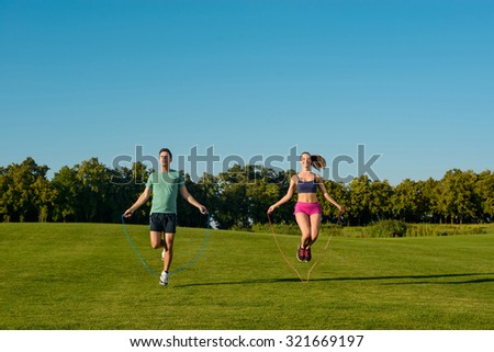 Sports on the street. Guy and girl are jumping on the jump rope. Young sportsmen do warm-up on a golf course.