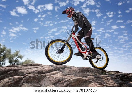 Sportsman in sportswear on a mountain bike rides on the stones in the extreme style of downhill