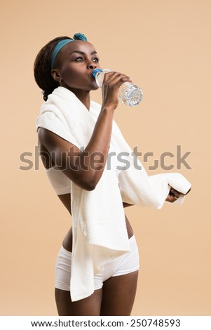 Sporty african woman drinking water from bottle. Fit sexy body