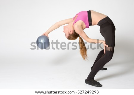 Sporty attractive blond young woman in sportswear working out indoors, doing variation of Standing Backward Bend posture, Ardha Chakrasana, Half Wheel pose full length.