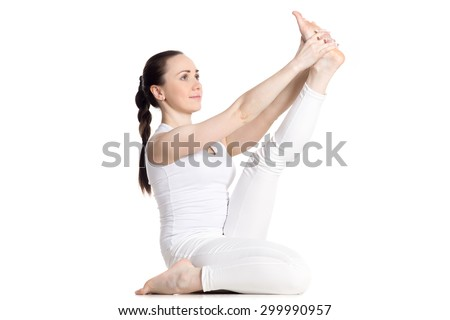 Sporty beautiful young woman in white sportswear doing exercises for legs, sitting in Krounchasana Pose, studio full length isolated shot, three-quarters view, part of large photo series