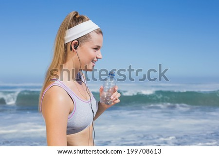 Sporty blonde on the beach drinking water on a sunny day