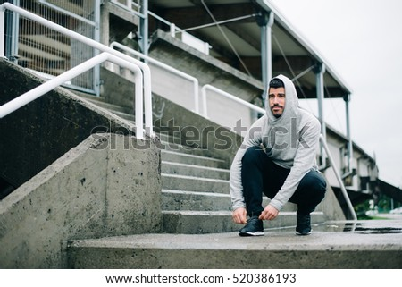 Sporty man getting ready for winter urban running and outdoor fitness workout. Sportsman lacing sport shoes on wet stairs.