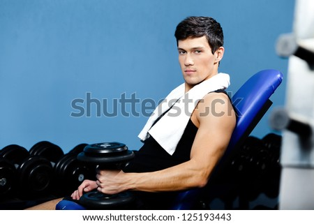 Sporty man in sportswear rests holding a weight in the hand against a set of dumbbells