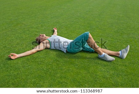Sporty young man laying on green training field with his arms spread, relaxing.