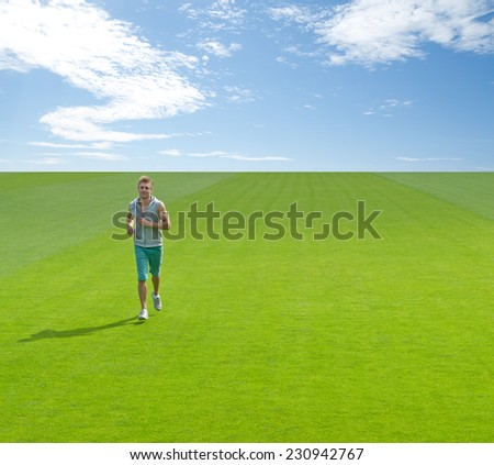 Sporty young man running on green field, under blue sky.