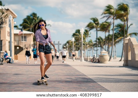 Sporty young woman riding long board on Hollywood beach in Miami, florida. Filtered image.