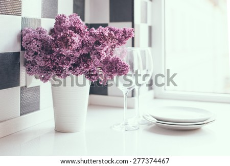 Spring bouquet of lilacs in a vase and glasses on the kitchen table by the wall, home interior