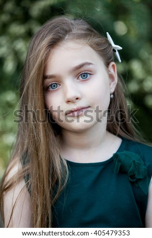 Portrait of beautiful little girl with brownish blond hair and blue eyes  standing