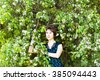 Spring girl portrait. Asian woman smiling happy on sunny summer or spring day outside in flowering tree garden. Pretty mixed race Caucasian or Chinese Asian young woman outdoors. - stock photo